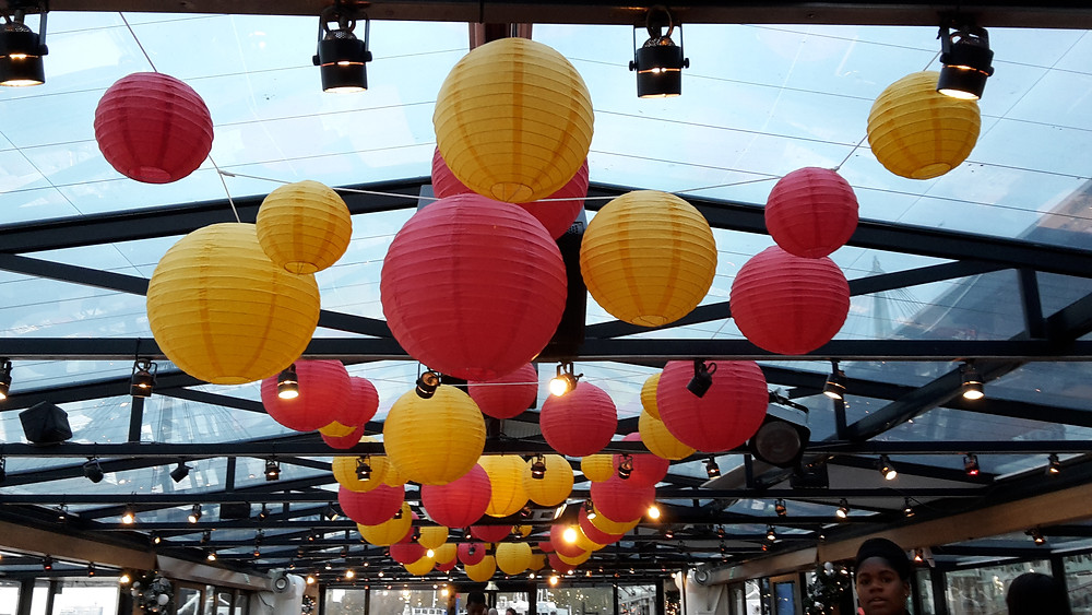 yellow and red round paper lanterns hung from the roof space of the symphony on the thames