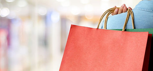 hand-holding-red-shopping-bag-blur-store