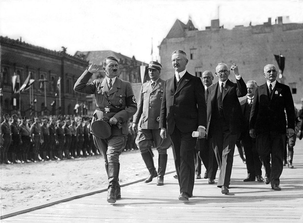 Hjalmar Schact (in stride with Hitler), President of the Reichsbank until 1939 and financier who rescued the German mark in 1923. A decade later he crafted loans and financing arrangements that allowed Nazi Germany to rearm in violation of the Versailles Treaty following WWI.