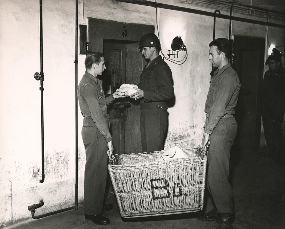 German POWs return laundry to prisoners under guard