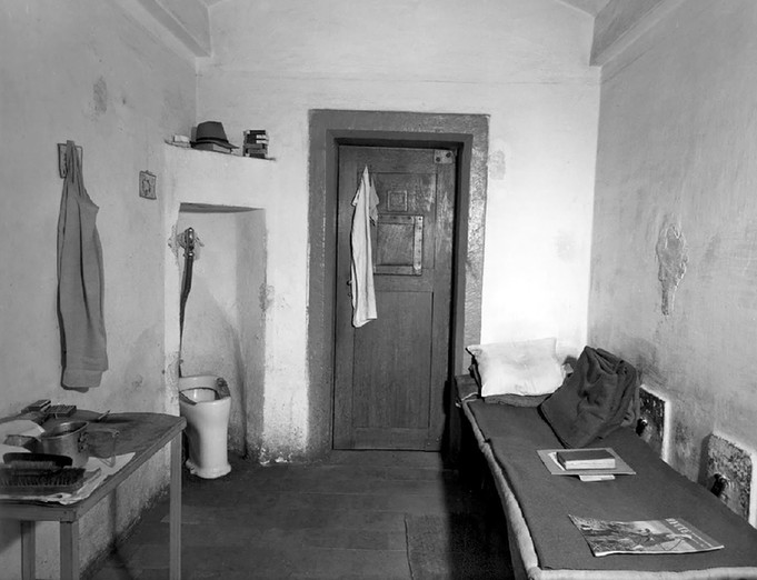 Interior of a cell in Nuremberg jail, approximate dimensions 9' x 13'. Glass on one small window with bars was replaced with unbreakable plastic for suicide prevention.