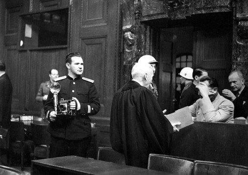 Soviet photographer Yevgeny Khaldei waits for an opportunity to photograph Herman Goering, who is consulting with his defense counsel