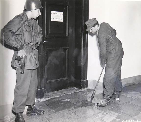 German POW mops under military supervision outside the British judges' office