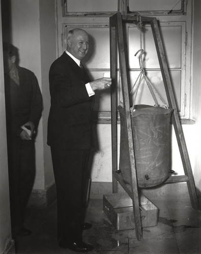 """In the halls of the Palace of Justice, a """"lister bag"""" serves up drinking water with chlorine added. 20,000 dead bodies were still buried amidst the rubble in Nuremberg, and the water was not safe to drink."""