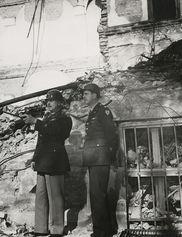 Head of Internal Security and Prison Commandant, Colonel Burton Andrus, surveys bomb damage in a part of the Palace of Justice with a staff member