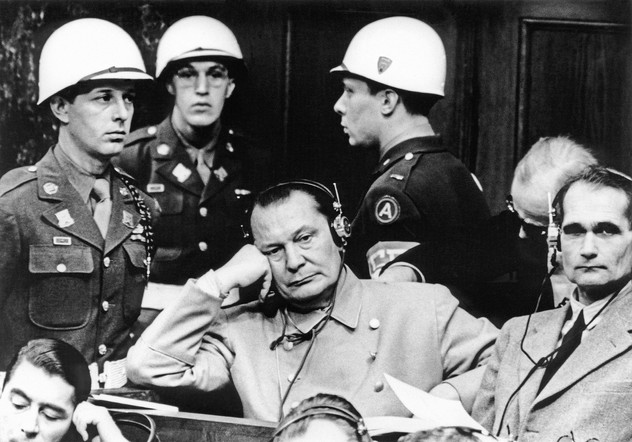 Herman Goering under guard in the courtroom, next to Rudolph Hess.