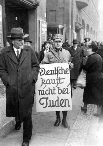 April 1, 1933: Recently elected Nazis under Julius Streicher organized a one-day boycott of all Jewish-owned businesses in Germany. An SA officer carries a sign through Berlin that reads: 'Germans don't buy from Jews.'