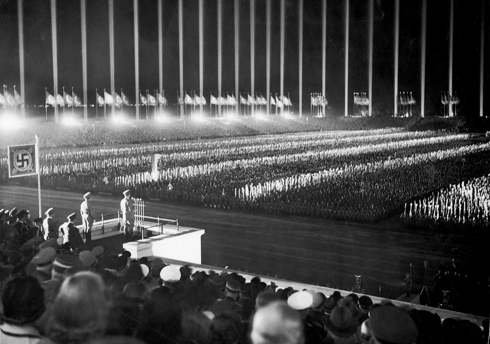 Hitler addressing a crowd of several hundred thousand at the 1937 Nuremberg Rally. Over 150 anti-aircraft search lights were used to create columns of light around the stadium's perimeter, seemingly extending to infinity.