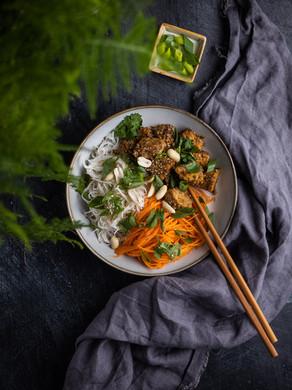 Bol au tempeh au sésame et nouilles de riz avec juliennes de carottes.