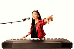 Young female musician playing a digital piano, singing on a microphone and pointing isolat