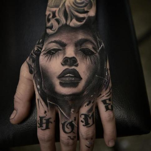 Tattoo of girl on man's hand