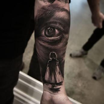 Tattoo of eye looking over little girl