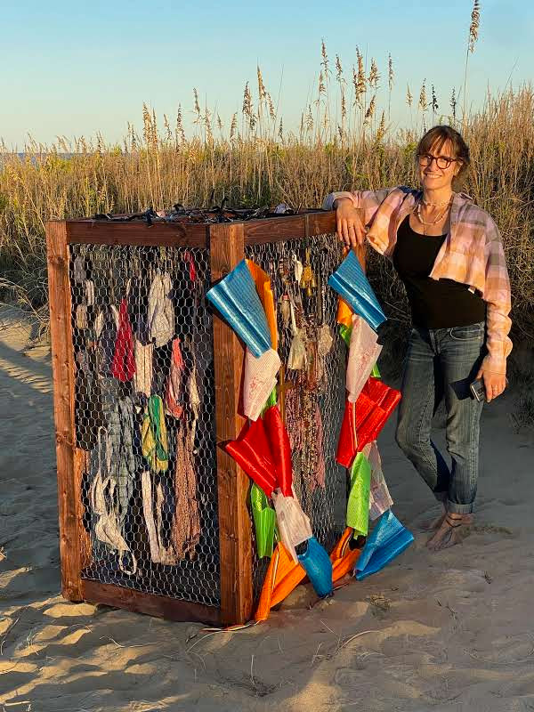 Kim McCoy, artist stands by the Hear their Voices exhibit, a box made of wired frames with fabric items attached on all sides. It sits on the sand with dune plants in the background.