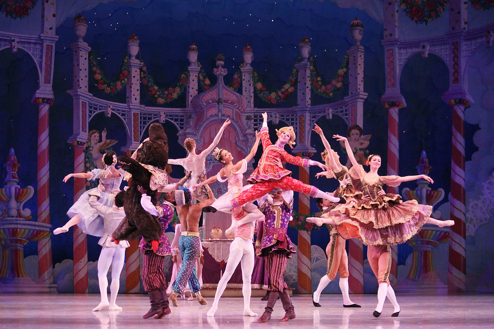 Ballet dancers onstage, half are holding up the other half while they leap