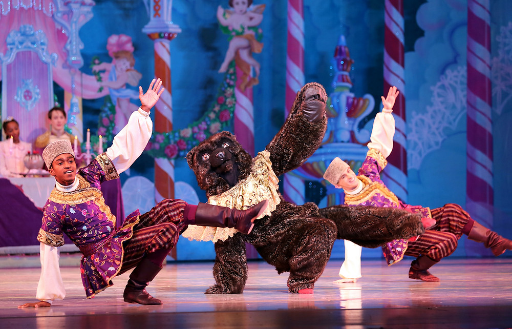 Three men (the center one in a bear costume) dance.