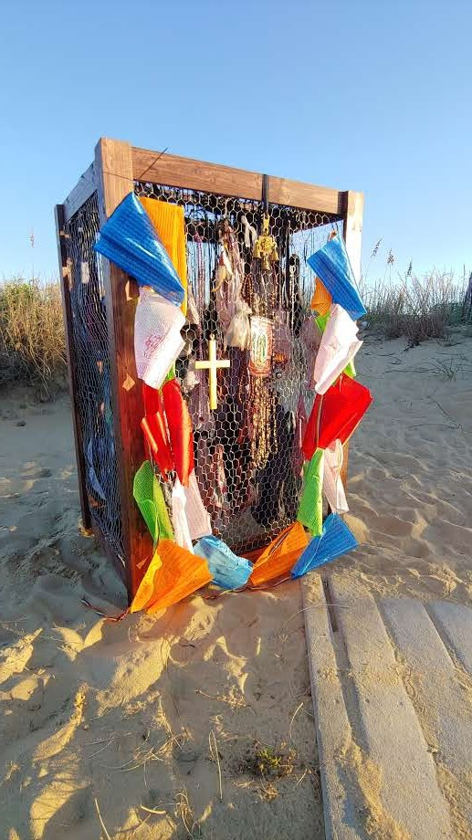 The piece sits on the sand with the sun streaming through the wire that makes up the sides.