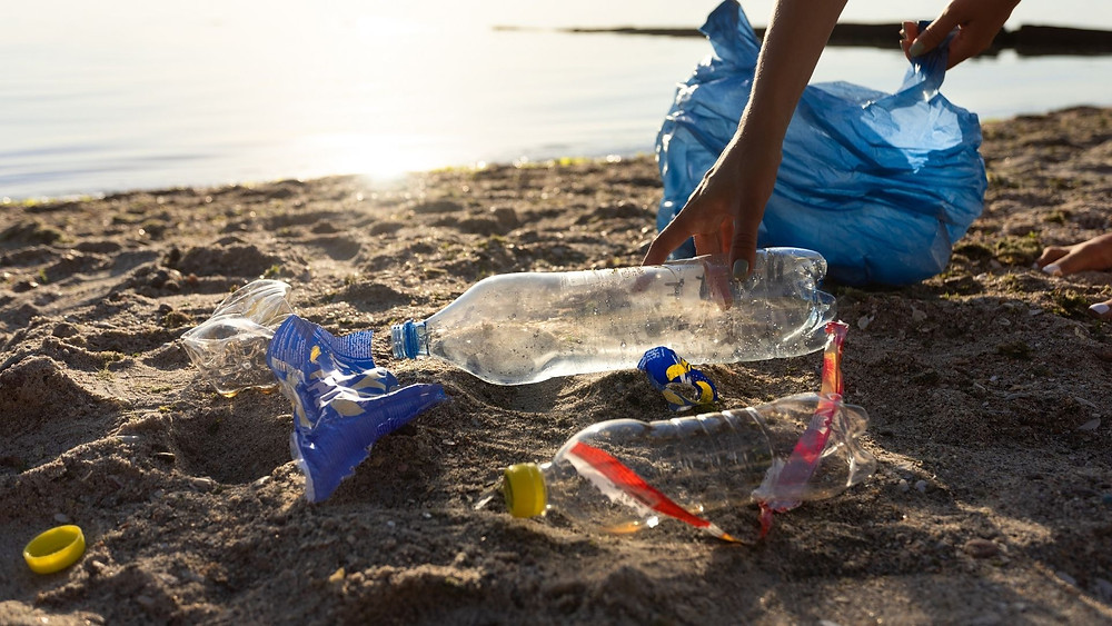 A hand reaches down to pick up plastic bottles on a beach. The other visible hand carries a trashbag.