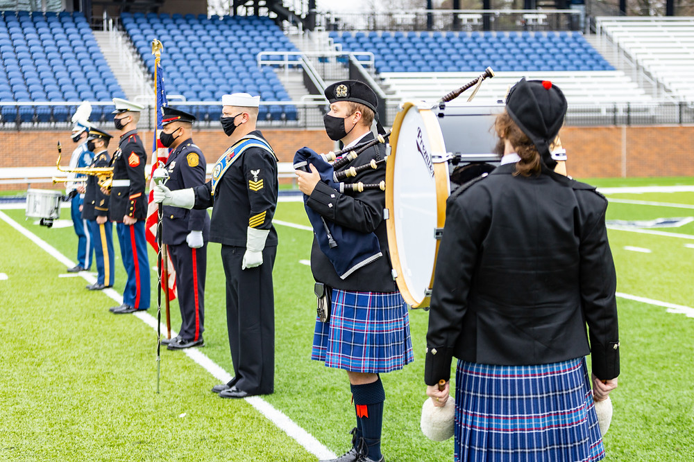 A line of drummers, pipers, brass musicians, a flag bearer and a drum major standing at attention on a football field for the Tattoo press conference. They are wearing their military uniforms, or the Tattoo tartan kilts (depending on what would be appropriate)