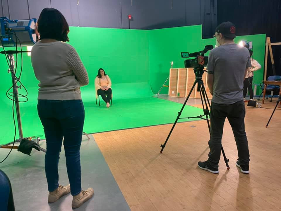 Aliki sits on a chair in front of a green screen, with a film crew surrounding her, all socially distanced and wearing masks