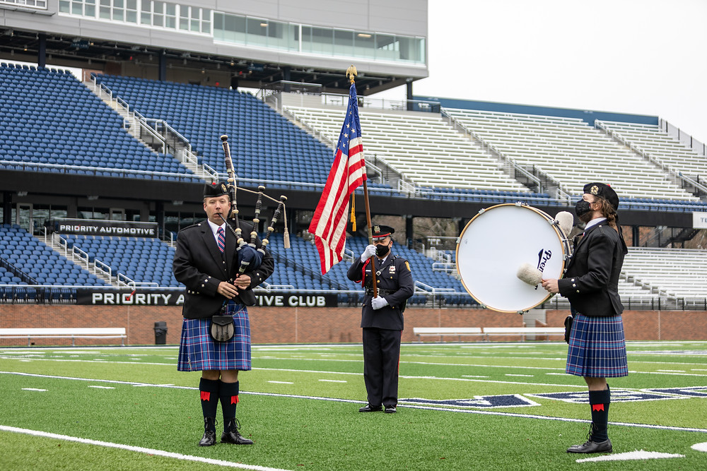 A piper, a drummer, and the american flag bearer on the football field.