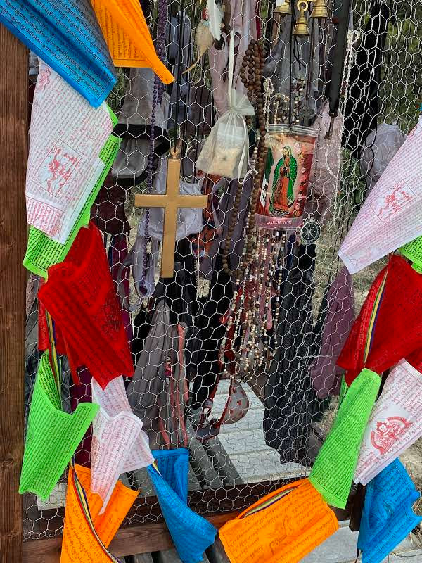 A closeup of one side of the exhibit, with crosses, peach flags, satchels, beads, bells, etc.