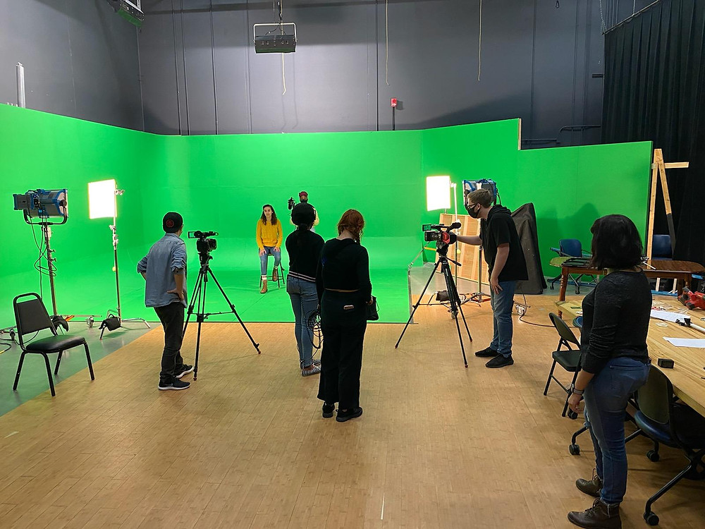Moriah sits on a chair on a green screen stage, with a socially distanced film crew surrounding her