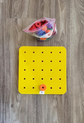 The same peg board, now with a stack of 4 pegs on one side of the board.