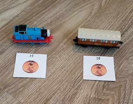 "A picture of two toy trains, each with a ""price tag"" in front of them. Both ""price tags"" have a penny printed on them with the text ""1 cent."""
