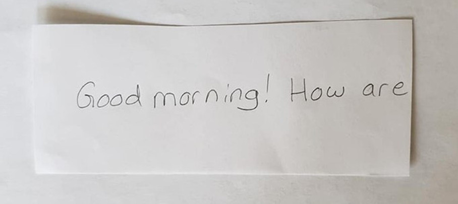 "An index card that reads, ""Good morning! How are "" The word ""you"" is cut off with scissors."