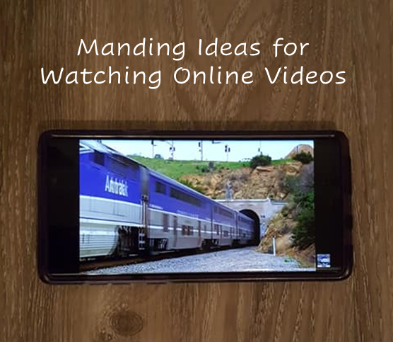 A picture of a cel phone displaying a video of a blue train moving on a track.
