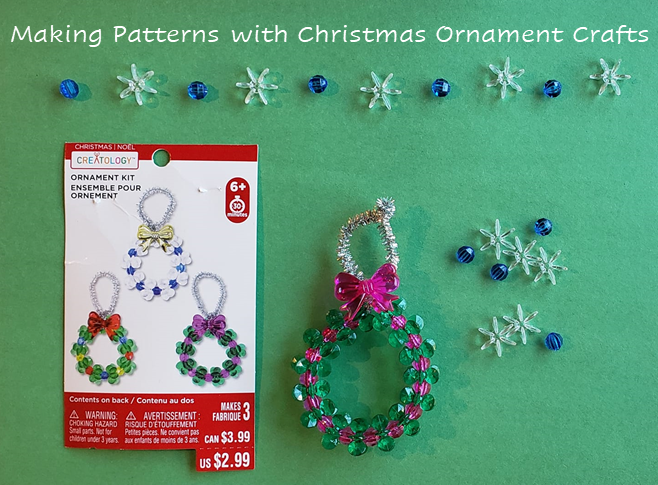 A picture of a completed wreath ornament with green and purple beads, alternating colors. A purple bow is glued at the top and it has a silver pipe cleaner for the hanger. Above the ornament are a series of blue and white beads in an AB pattern, ready to make a second ornament.