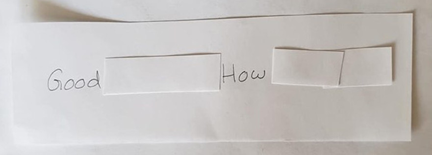 "An index card that reads, ""Good morning! How are you?"" The words you, are, and morning are covered up by a small piece of paper."