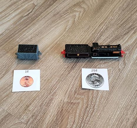 A photo of two toy trains, one with a price tag of one cent and one with a price tag of 25 cents.