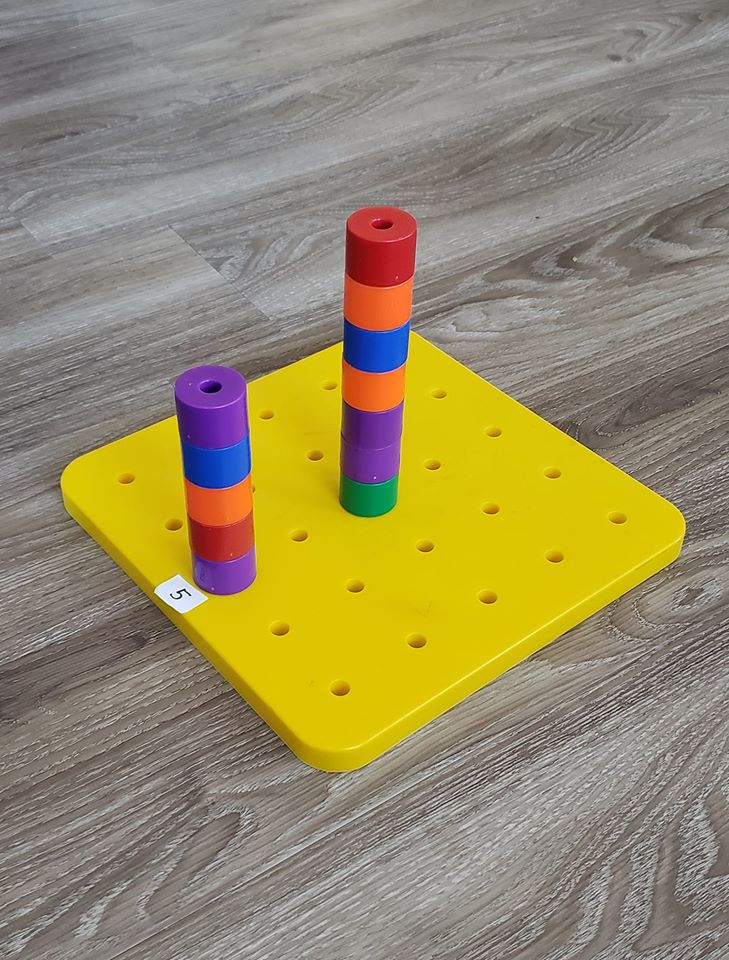 A pebboard with a tall tower in the middle space.