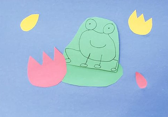 Frog, flowers, and lily pads cut out of construction paper and glued on a piece of blue construction paper to look like a pond.