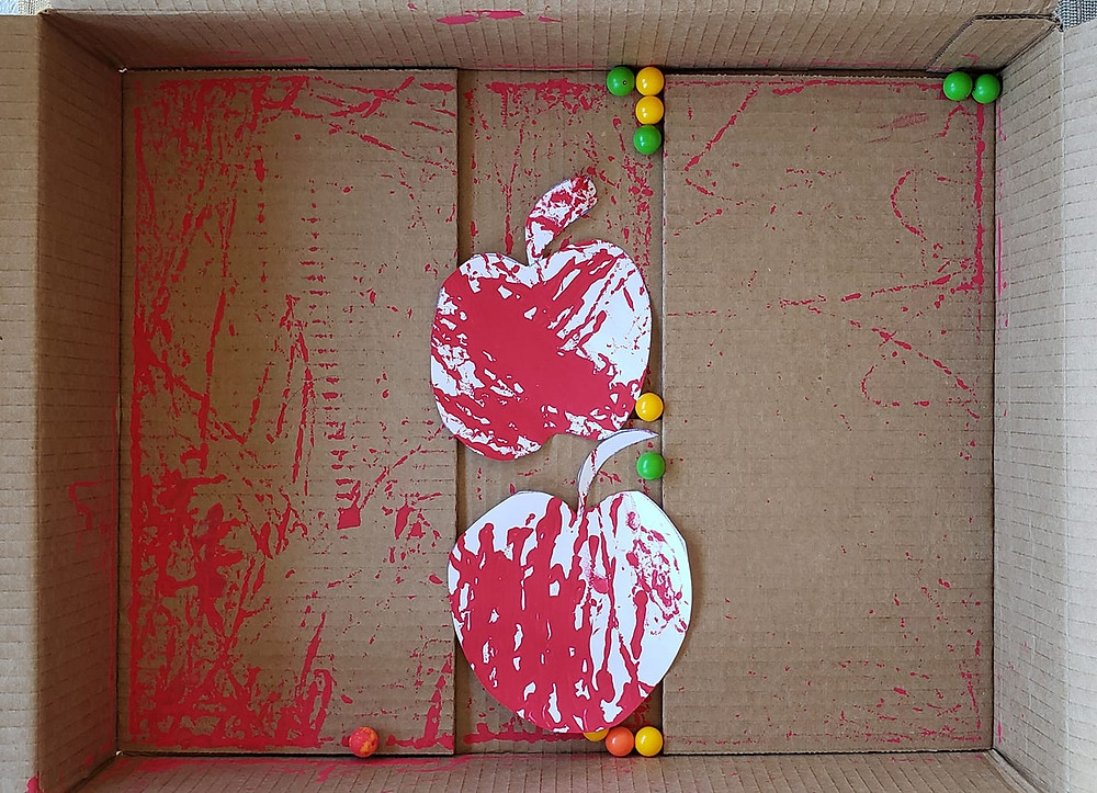 A cardboard box with marbles and apple shapes cut out of paper inside. The marbles are covered in red paint and streaks of paint are also on the paper apples.