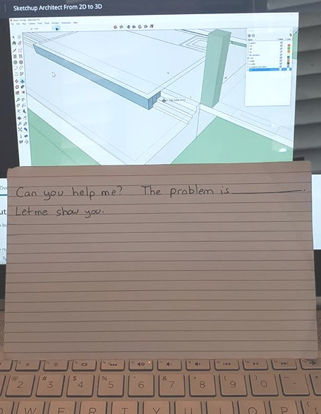 "In image of a card in front of a computer screen. The card reads, ""Can you help me? The problem is ______. Let me show you."""