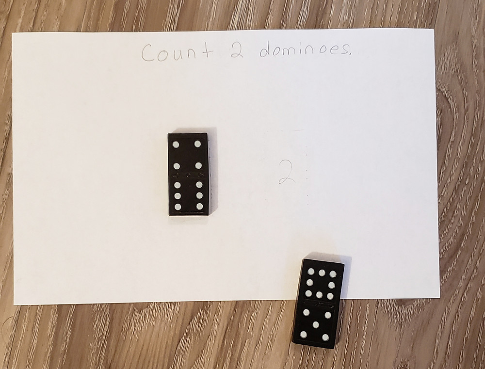 "A piece of paper with the numbers 1, 2 written on it, one place for each of 7 dominoes. The words, ""give me 2 dominoes"" are written on the paper."