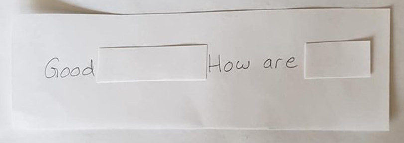 "An index card that reads, ""Good morning! How are you?"" The words ""you"" and ""morning"" are covered up by a small piece of paper."