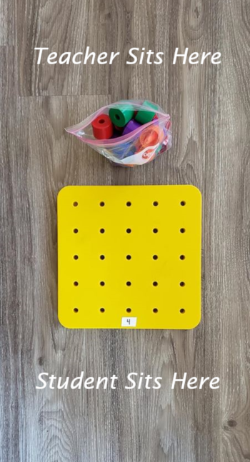 "A toy pegboard from Discovery Toys. The pegs are in a bag that the teacher holds. There is a small piece of paper with the number ""4"" written on it in front of one of the holes on the pegboard."