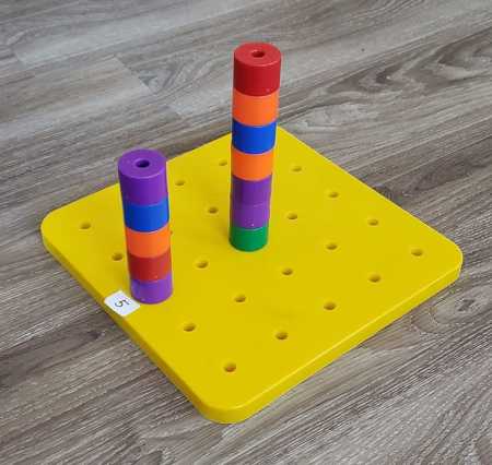 An image of a pegboard with a tower built in the middle.