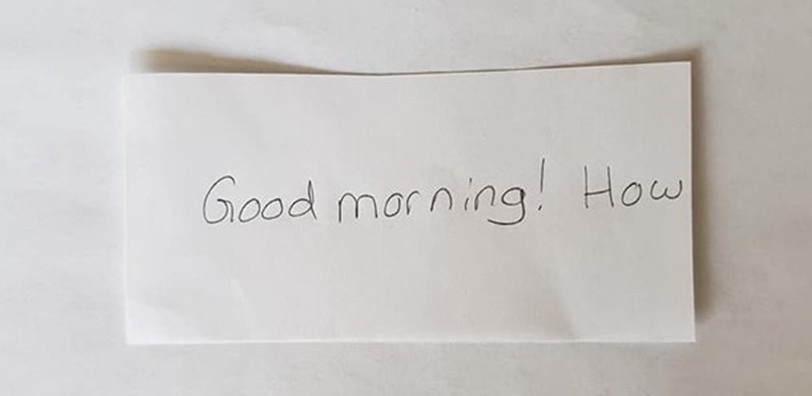 "An index card that reads, ""Good morning! How "" The words ""you"" and ""are"" are cut off with scissors."