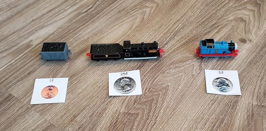 A photo of three toy trains, each with a different price tag in front of them (one cent, 25 cents, and 5 cents).