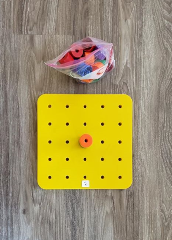 The same peg board with the stack of 4 pegs moved to the middle. A new piece of paper has been placed at the edge of the board. The piece of paper has a numeral 2 written on it.