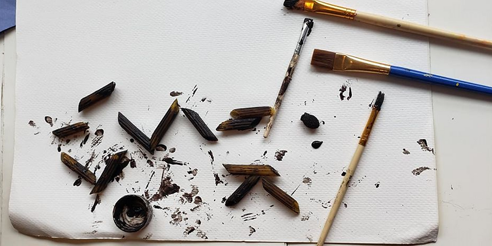 Four paintbrushes and several pasta noodles painted black.