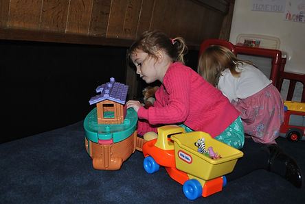 Young children playing next to a black Cooltouch heater.