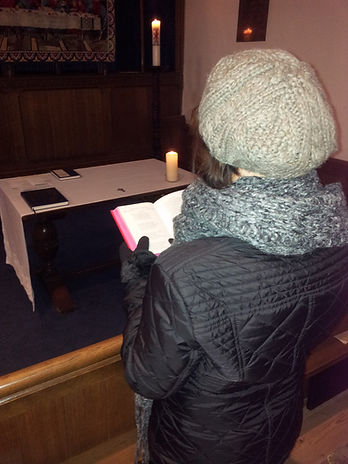 Person wrapped up in winter clothes in cold church