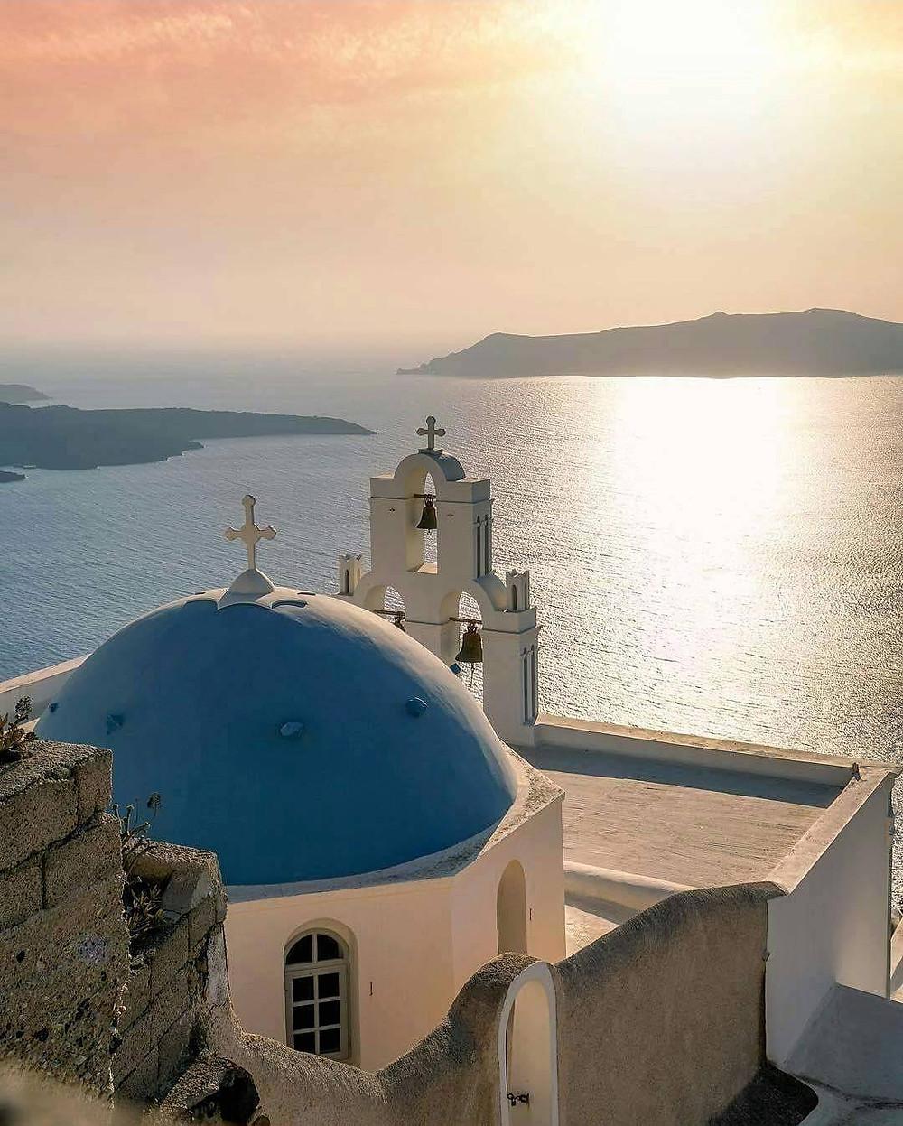 matrimonio a santorini chiesa con tetto blu al tramonto e vista mare