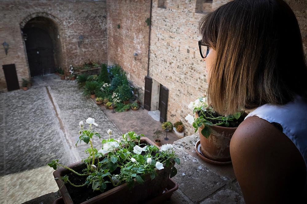 Donna che guarda dall'alto la corte interna del Castello di Santarcangelo