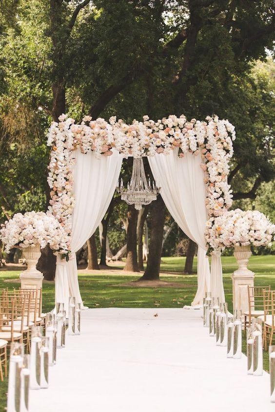 Matrimonio all'aperto: arco di tessuto e fiori in un bosco